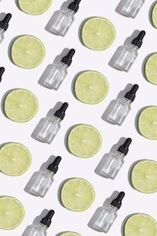 Vue de dessus du flacon compte-gouttes de sérum de vitamine c, d'huile cosmétique et de tranches de citron vert sur fond blanc. format vertical de modèle de cosmétiques créatifs