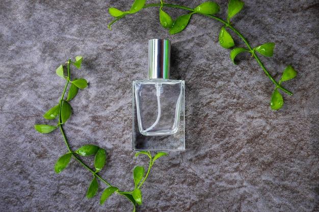 Vue de dessus du flacon de parfum entouré de feuilles vertes