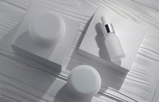 Vue de dessus du flacon pipet blanc et des contenants de crème sur une surface en bois blanche