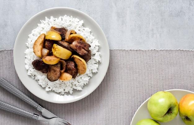 Vue de dessus du foie de poulet frit aux pommes servi avec du riz blanc sur une assiette