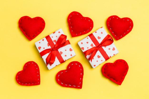 Vue de dessus du fond coloré de la saint-valentin composé de coffrets cadeaux et de coeurs en textile rouge.