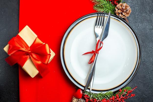 Vue de dessus du fond de noël avec des couverts avec ruban rouge sur une assiette à dîner accessoires de décoration branches de sapin à côté d'un cadeau sur une serviette rouge