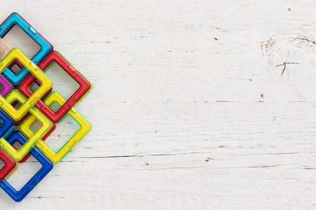 Vue de dessus du fond de table en bois blanc avec des formes en plastique colorées et des pièces magnétiques