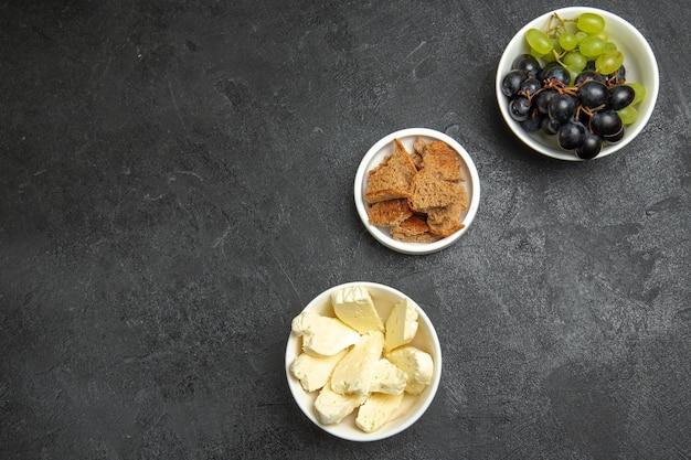Vue de dessus du fromage blanc avec des raisins frais sur une surface sombre, des aliments aux fruits, du lait, du pain