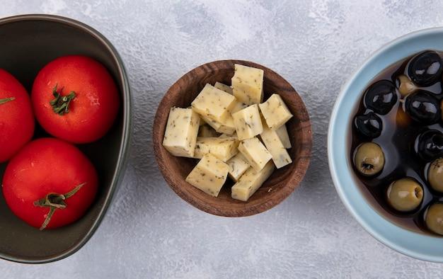 Vue de dessus du fromage sur un bol en bois avec des tomates et des olives sur fond blanc