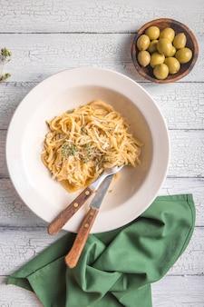 Vue de dessus du fromage crémeux, des olives, des pâtes fettucini alfredo.