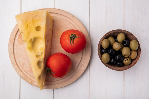 Vue de dessus du fromage maasdam aux tomates sur un support avec des olives sur fond blanc