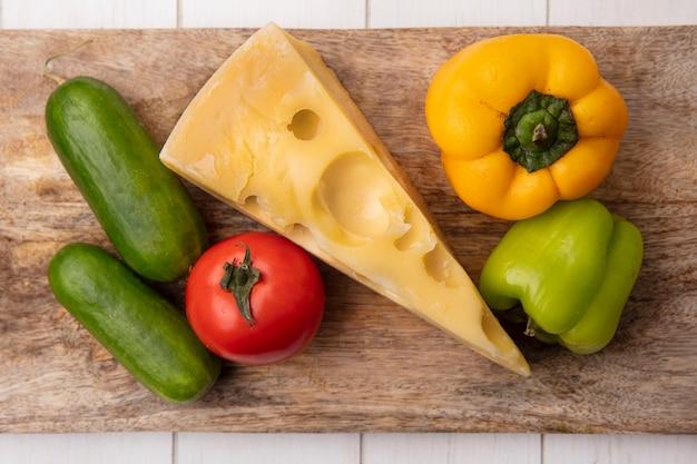 Vue de dessus du fromage maasdam avec concombres, tomates et poivrons sur un support