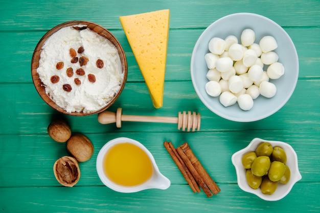 Vue de dessus du fromage mozzarella dans un bol de fromage cottage et un morceau de fromage hollandais avec des bâtons de cannelle au miel de noix et des olives marinées sur bois vert