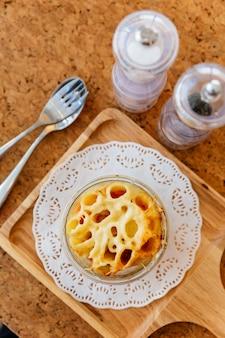 Vue de dessus du fromage penne au four dans un bol en verre sur une plaque en bois avec du sel, du poivre et des couverts.