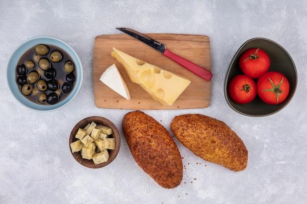 Vue de dessus du fromage sur une planche de cuisine en bois avec couteau avec galettes de tomates et olives sur fond blanc