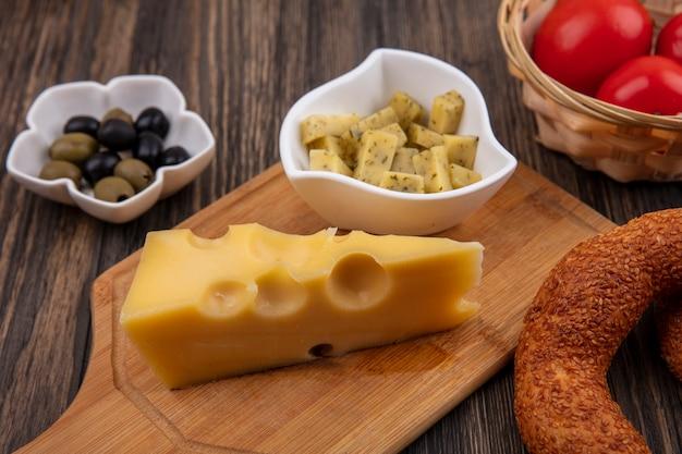 Vue de dessus du fromage avec des tranches de fromage sur un bol sur une planche de cuisine en bois avec des olives sur un bol sur un fond en bois