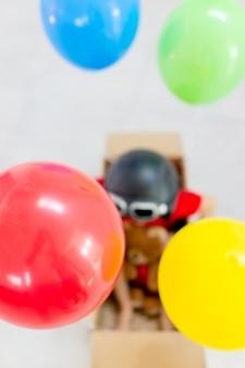 Vue de dessus du garçon assis dans une boîte avec des ballons