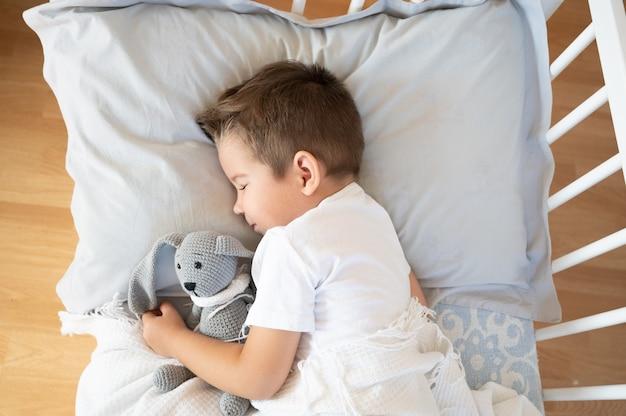 Vue de dessus du garçon endormi allongé sur le lit avec un jouet de lapin dans ses mains. photo de haute qualité