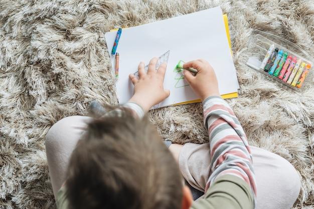 Vue de dessus du garçon en train de peindre à la maison