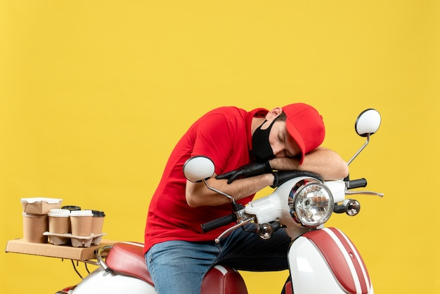 Vue de dessus du gars de courrier fatigué portant un chemisier rouge et des gants de chapeau dans un masque médical délivrant une commande assis sur un scooter