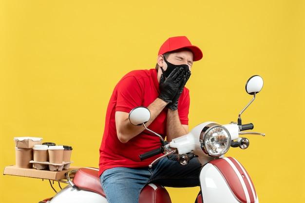 Vue de dessus du gars de messagerie en difficulté portant un chemisier rouge et des gants de chapeau dans un masque médical délivrant l'ordre assis sur un scooter souffrant de maux de dents