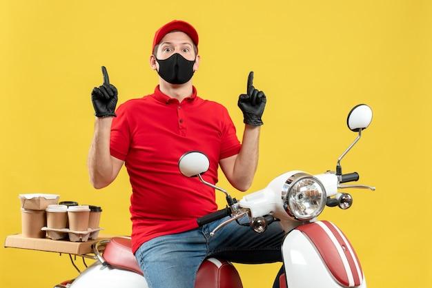 Vue de dessus du gars de messagerie surpris portant chemisier rouge et gants de chapeau en masque médical délivrant l'ordre assis sur un scooter pointant vers le haut