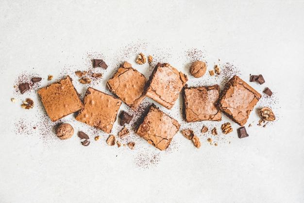 Vue de dessus du gâteau au brownie fait maison fraîchement cuit coupé en carrés sur blanc rustique.