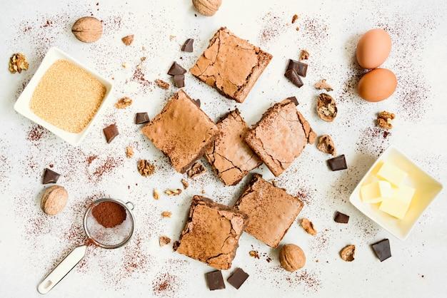 Vue de dessus du gâteau au brownie fait maison fraîchement sorti du four, arrangé avec des noix, du chocolat et de la poudre de cacao sur blanc rustique.