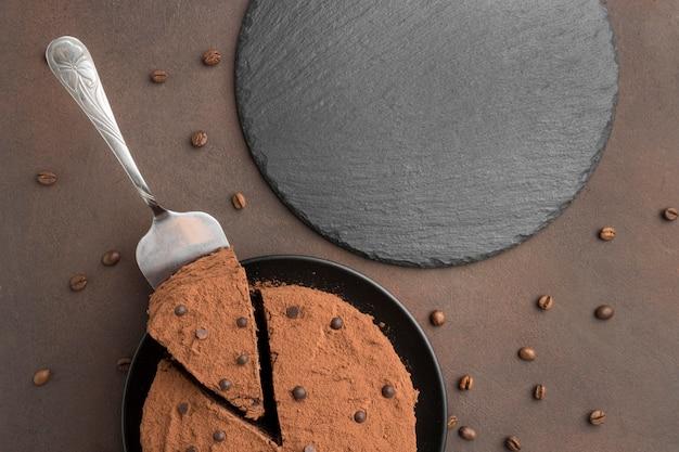 Vue de dessus du gâteau au chocolat avec du cacao en poudre et des grains de café