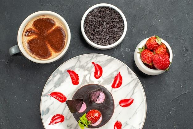 Vue de dessus du gâteau au fromage aux fraises sur des bols à assiette ovale blanc avec des fraises et du chocolat une tasse de café sur fond sombre