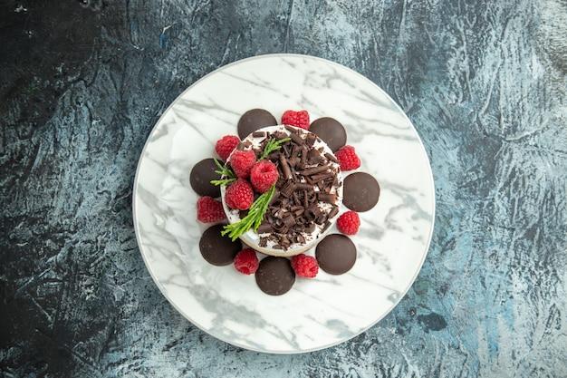 Vue de dessus du gâteau au fromage avec du chocolat sur une plaque ovale blanche sur l'espace libre de surface grise