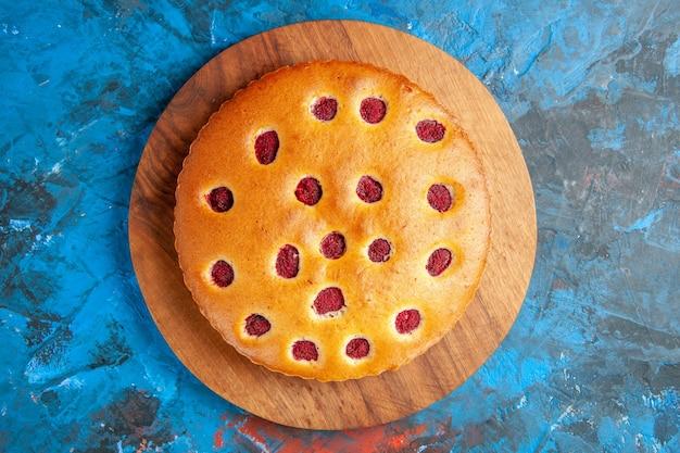 Vue de dessus du gâteau aux fraises sur planche de bois sur une surface bleue