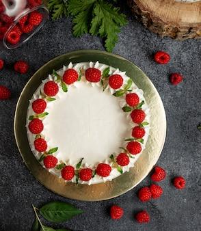Vue de dessus du gâteau aux framboises décoré de framboises à la crème blanche et de feuilles de menthe