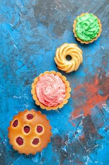 Vue de dessus du gâteau aux framboises en diagonale biscuit petites tartelettes sur surface bleue
