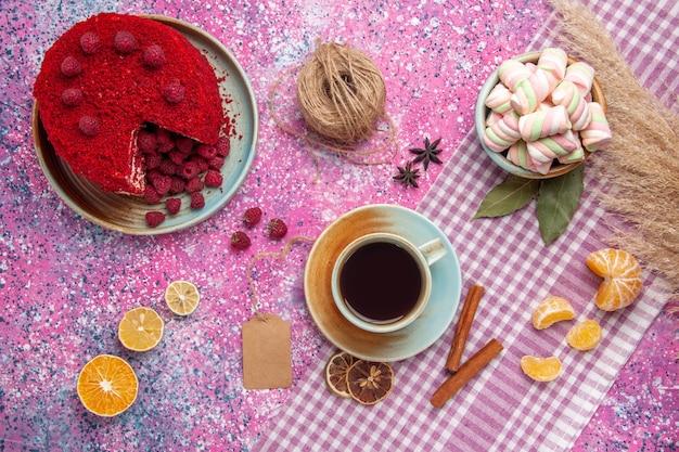 Vue de dessus du gâteau aux framboises rouges avec des mandarines à la cannelle et du thé sur la surface rose