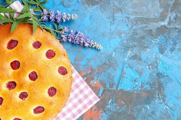 Vue de dessus du gâteau aux framboises sur une serviette de cuisine sur une surface bleue