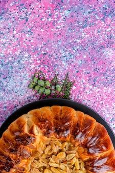 Vue de dessus du gâteau aux raisins secs gâteau à la tarte au four rond formé sur une surface rose