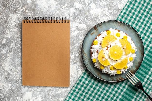 Vue de dessus du gâteau avec de la crème pâtissière et du citron sur une assiette une fourchette sur une nappe à carreaux blanc vert. cahier vide