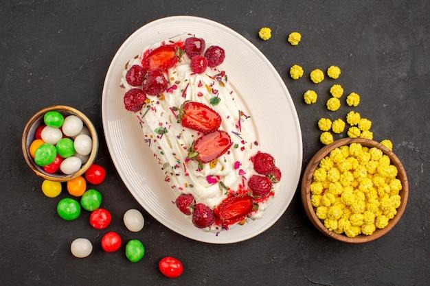 Vue de dessus du gâteau crémeux fruité avec des bonbons sur fond noir