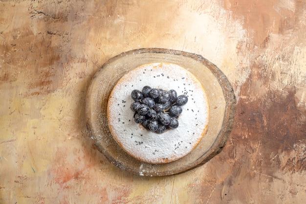 Vue de dessus du gâteau un gâteau aux raisins noirs et sucre en poudre sur la planche à découper