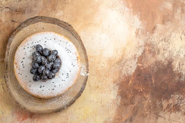 Vue de dessus du gâteau un gâteau avec du sucre en poudre et des raisins noirs sur la planche à découper
