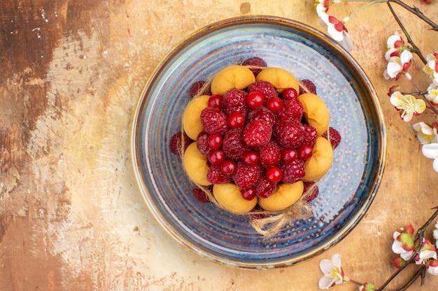Vue de dessus du gâteau moelleux fraîchement sorti du four avec des fruits et des fleurs sur la table de couleurs mixtes