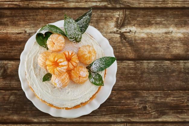 Vue de dessus du gâteau nu de mandarines avec des feuilles sur fond rustique.