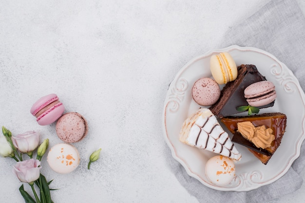 Vue de dessus du gâteau sur la plaque avec des macarons et rose