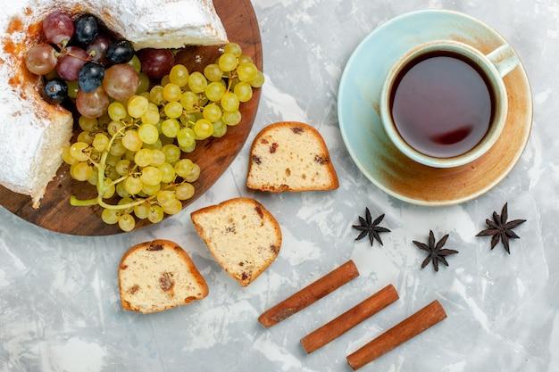 Vue de dessus du gâteau en poudre délicieux gâteau cuit au four avec des raisins frais et du thé sur un bureau blanc