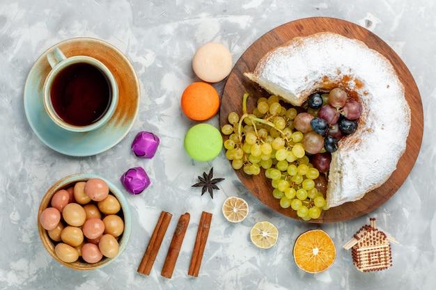 Vue de dessus du gâteau en poudre avec du thé aux raisins frais et des macarons français sur un bureau blanc