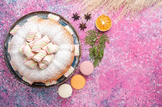 Vue de dessus du gâteau en poudre de sucre avec des guimauves sucrées et des macarons sur une surface rose