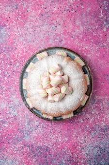 Vue de dessus du gâteau en poudre de sucre avec des guimauves sur la surface rose