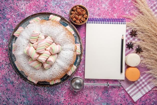 Vue de dessus du gâteau en poudre de sucre avec des macarons et bloc-notes sur une surface rose clair