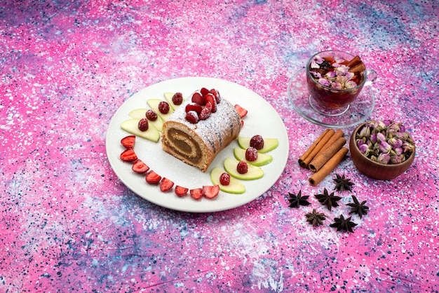 Vue de dessus du gâteau de rouleau à l'intérieur de la plaque avec des pommes et des fraises avec de la cannelle et du thé sur le gâteau de bureau de couleur biscuit pâte au chocolat
