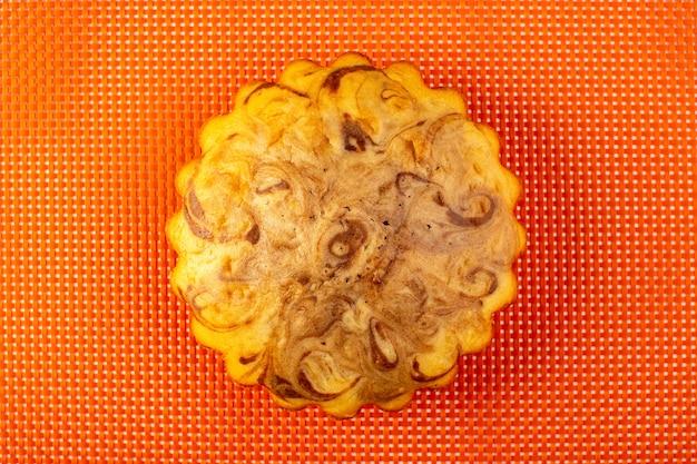 Une vue de dessus du gâteau sucré rond délicieux gâteau au chocolat délicieux sur le fond orange à carreaux biscuit au thé au sucre cuire au four
