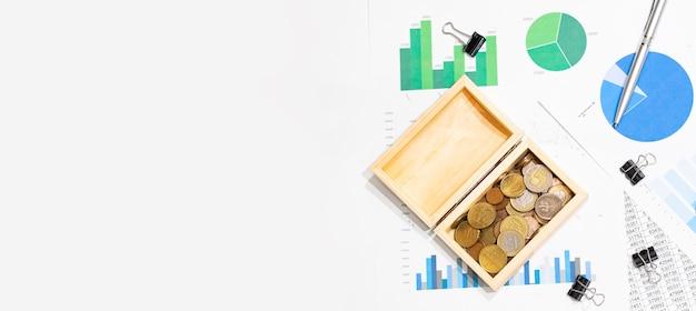 Vue de dessus du graphique d'entreprise sur une table en bois blanche avec des pièces de monnaie, une boîte en bois et un stylo. mise à plat