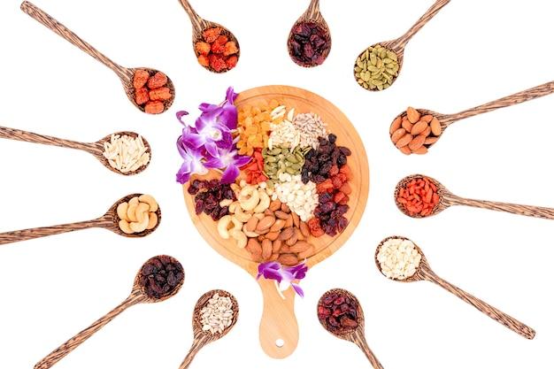 Vue de dessus du groupe de grains entiers et de fruits secs 12 sortes avec une belle orchidée sur une assiette en bois et des cuillères en bois isolées sur fond blanc.