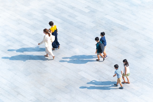 Vue de dessus du groupe de mères et d'enfants marchant sur une passerelle piétonne en plein air pour voyager